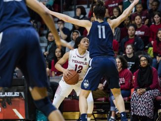 Freshman guard Emani Mayo (center) looks for an open teammate while marked by UConn senior guard Kia Nurse in the Owls' 113-57 loss on Sunday at McGonigle Hall. | SYDNEY SCHAEFER / THE TEMPLE NEWS
