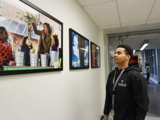 Freshman neuroscience major Daniel Gilliam looks at photographs of former First Lady Michelle Obama in Paley Library. The photos were taken by Amanda Lucidon and are on display until Jan. 22. | CACIE ROSARIO / THE TEMPLE NEWS