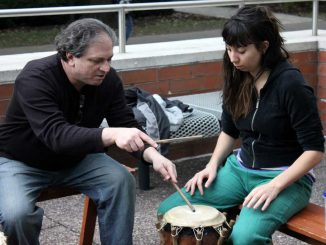 Dan Gorlin teaches a student how to play drum on Oct. 14. Gorlin is the founder of Alokli African Dance, a drum circle that meets Sundays on Main Campus. ( SABA AREGAI // TTN )