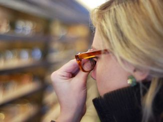 """An attendee of Warby Parker's """"class trip"""" tour tries on a pair of frames inside of the schoolbus showroom. The bus is touring major cities across the U.S. 