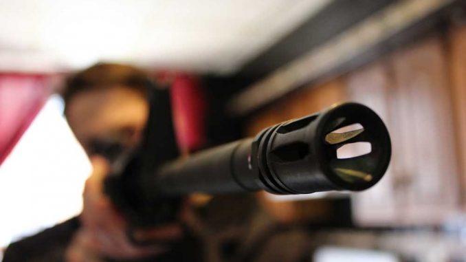 Senior Mark Edwards displays a firearm in his off-campus apartment. | ELLEN PARKINS / TTN