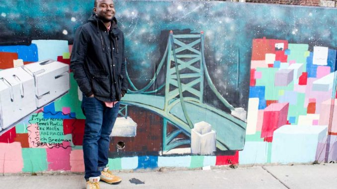 Donnell Powell stands next to a mural commissioned through his first nonprofit. | LUIS FERNANDO RODRIGUEZ / TTN