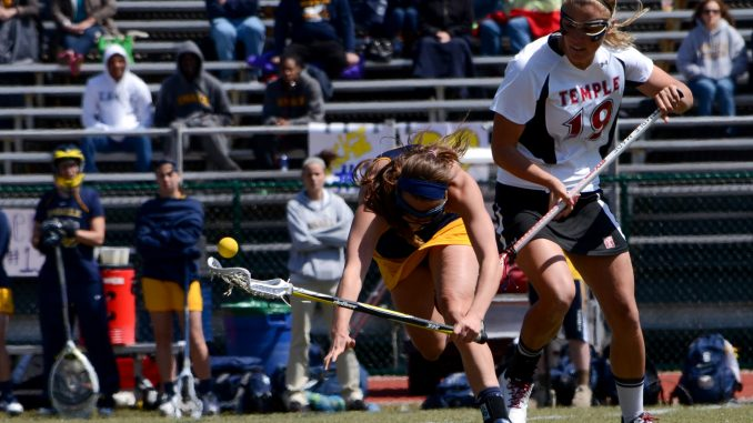 Freshman attack Summer Jaros (right) checks an Explorer in the Owls' 14-13 loss on Sunday. | DANIEL PELLIGRINE / TTN