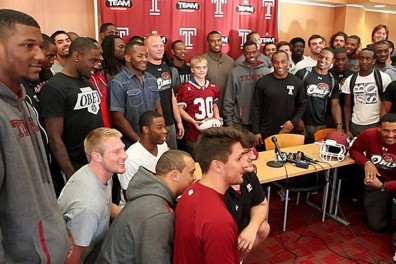 "Chris Richer (middle), a 15-year-old boy, was ""adopted"" by the football team. 