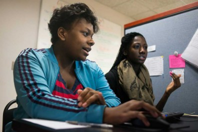 Michelle Samys (left) attends her fourth visit to LIFT North Philadelphia. Temple student DiAsia Dozier is helping her work on her college applications, including writing and filling out forms. | Abi Reimold TTN