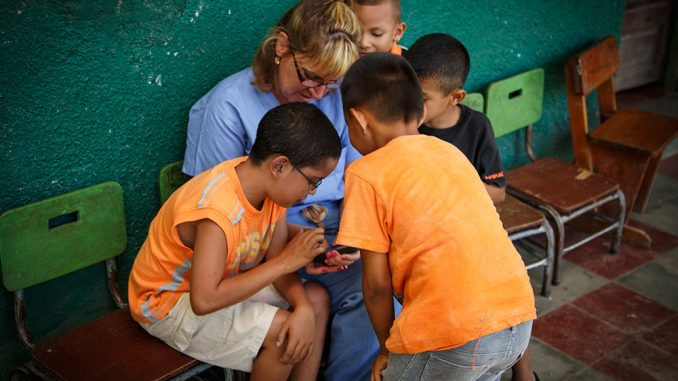 Suzanne Durocher works with children in Honduras this past summer as part of a clinical tour. | COURTESY LINA KHONG