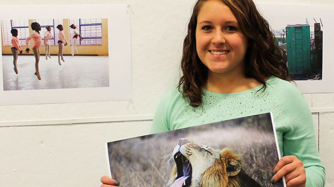 Kelsey Dubinsky holds the photo she took in South Africa of a wild lion mid-yawn in Kruger National Park of South Africa. | Sash Schaeffer TTN