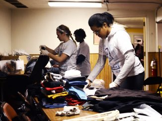 Volunteer Temple student Janice Durant, a junior communication studies major, folds donated clothes at Berean Presbyterian Church on Martin Luther King Jr. Day. | Andrew Thayer TTN