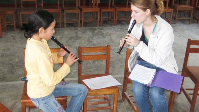 "Elizabeth Moulthrop practices the recorder with a student in Pisco, Peru in 2012 as a part of her ""Notes for Change"" program, where she aims to spread musical education throughout the country. 