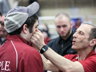 Coach Fred Turoff wipes a tear from sophomore Jon Rydzefski's face during the men's gymnastics team's final conference championship. | HUA ZONG TTN