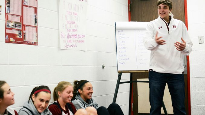Kat Longshore (right) talks to members of the lacrosse team during one of her sessions with the Owls. Longshore said she meets with the team at least once per week. | Andrew Thayer TTN