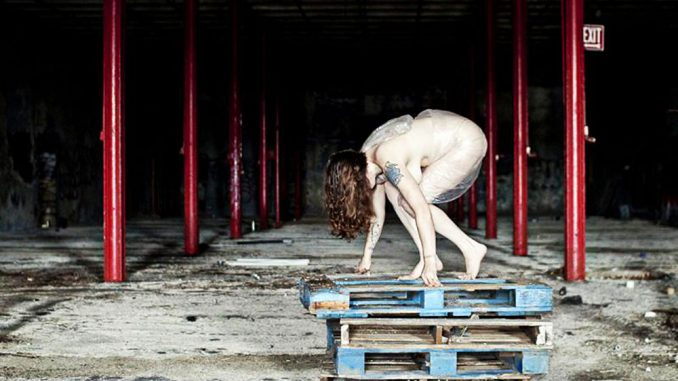 """Sarah Bloom poses for her series, """"Discarded,"""" in an abandoned building.