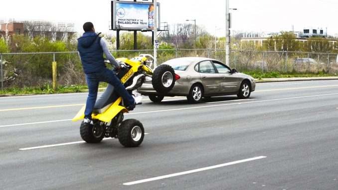 An ATV driver rides down Grays Ferry Avenue in 2012, while performing a wheelie. Andrew Thayer |TTN