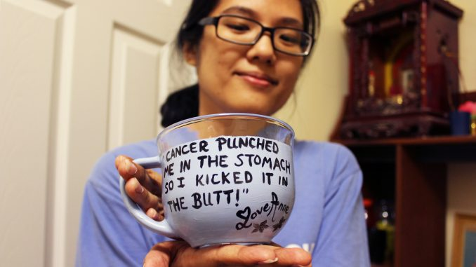 Anne Ha holds a glass cup she painted. After her diagnosis in June, Ha began decorating mugs and other items with her own inspirational quotes. Claire Sasko | TTN
