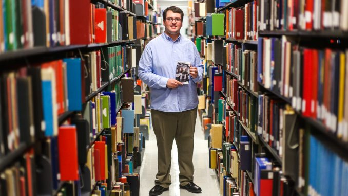 """Freshman journalism major Max Buchdahl stands in Paley library while holding his self-published book, """"Return of the Exiled."""" Andrew Thayer 