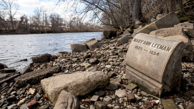 A tombstone sits on the banks of the Delaware River near the Betsy Ross Bridge. Several former grave markers from Monument Cemetery were used as foundation for the bridge. Kate McCann | TTN