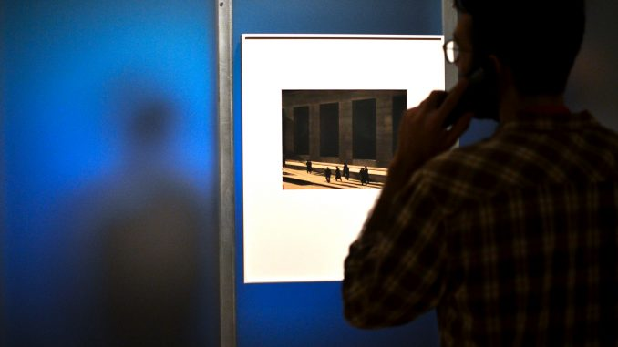 """A man views Paul Strand's photograph, """"Wall Street, New York"""" while other patrons watch Strand's first film, """"Manhatta."""" Jenny Kerrigan 