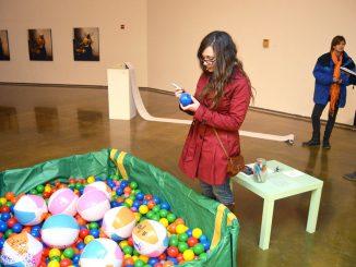 "Hannah Pigeon writes her own ""weird habit"" on a ball as part of an interactive exhibit. Greg Frangipani | TTN"