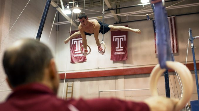 Longtime men's gymnastics coach Fred Turoff watches sophomore Casey Polizzotto practice on the rings in McGonigle Hall on Monday. | Kara Milstein TTN
