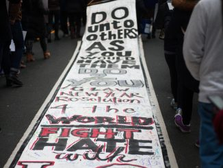 Marchers hold signs as they walk down Broad Street as part of a rally on Martin Luther King Jr. Day. | Skyler Burkhart TTN
