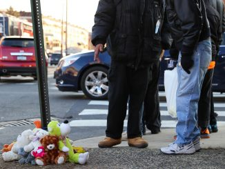 Community members gathered at the corner of 12th and Jefferson streets for a vigil honoring Kim Jones, 56, who was killed at the corner Tuesday morning. | JENNY KERRIGAN TTN