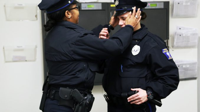 Officer Sherrelle Mitchell adjusts the hat of her colleague, Officer Melissa Tracton. Jenny Kerrigan | TTN