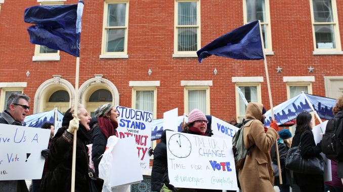 """Adjunct professors chant, """"Let us vote,"""" as they march down Liacouras Walk on Feb. 23. Pending a March 19 hearing with the Pennsylvania Labor Relations Board, adjuncts are demanding a vote for or against unionization. 