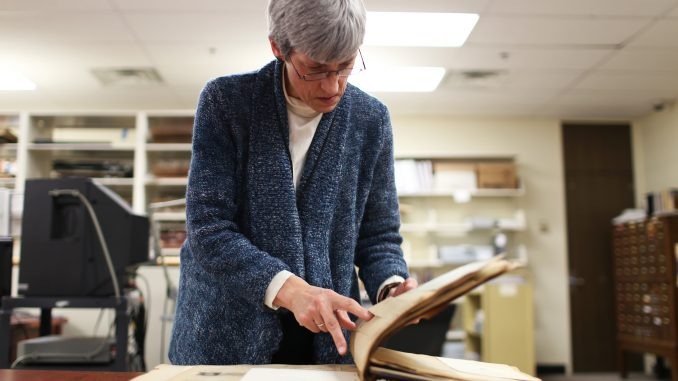 Margery Sly, director of the Special Collections Research Center, shows a historic volume available in Temple's Urban Archives. Administrators said more of the collections could be housed on Main Campus if packed tightly in the upcoming new library. | Kara Milstein TTN