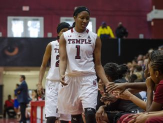 Junior guard Erica Covile and senior guard Tyonna Williams high-five teammates on their way to the bench during the Owls' 83-49 loss against Connecticut Feb. 1.   Bradley Vassalo TTN FILE PHOTO