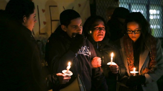 Alex Rojas-Garcia's sister Aleida Silva-Garcia (left), son Alex Jr., sister Enid Rojas and daughter Brianna hold candles at a vigil for him in Feltonville on Feb. 7.   JENNY KERRIGAN TTN