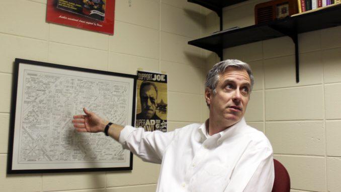 Joe Glennon, the faculty director of Diamond Edge Communications, motions to his favorite poster of Bruce Springsteen lyrics. Glennon's work has always focused on copywriting. | Grace Wilson TTN