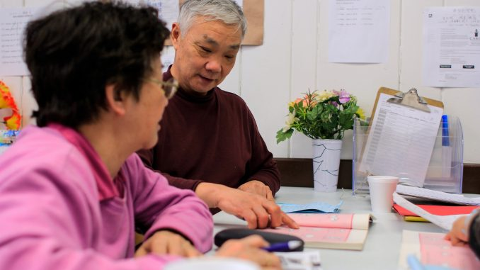 Muoi Thai, 68 (left), and Jiang Bogun, 65, practice English at the Coffee Cup Branch of the Philadelphia Senior Center on March 19. The two are students in the IGC's Project SHINE program. | Harrison Brink TTN