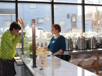 Employee Tara Scott offers a customer a sample of one of Good Spoon's signature soups. | Eamon Dreisbach TTN