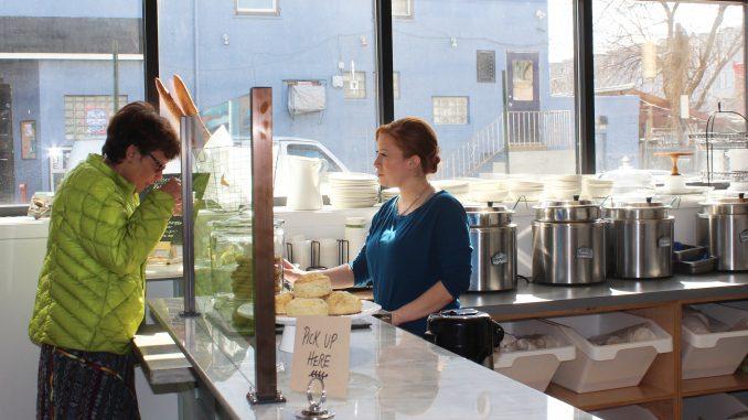 Employee Tara Scott offers a customer a sample of one of Good Spoon's signature soups. | Eamon Dreisbach TTN