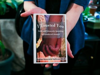 "Professor Rev. Dr. Nadine Rosechild Sullivan holds her book, ""I Trusted You"", which discusses violence against women. 