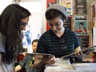 "Lauren DeLucca (left) and Rachel Dispenza, the organizers of ""Girls to the Stage,"" a compilation and benefit show, look through albums at Creep Records on Record Store Day. 