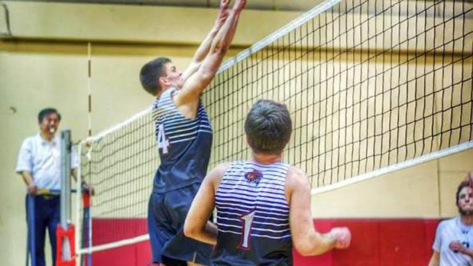 Freshman middle hitter Tyler Phifer attempts a block during a men's volleyball club match. | COURTESY Zack Hennigan