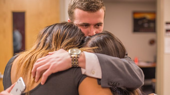 Ryan Rinaldi (center) hugs Brittany Boston (left) and Binh Nguyen after learning the result of the Temple Student Government election, which was announced Thursday. The three will take office on April 27. | Margo Reed TTN