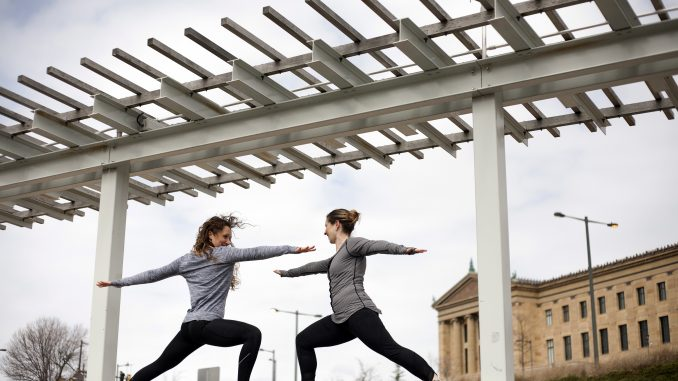 Nicole Beddow (left) and Justine Carmine assume yoga positions near the Philadelphia Museum of Art. 'Happy Hippy' will offer pop-up yoga classes to customers. | Skyler Burkhart TTN