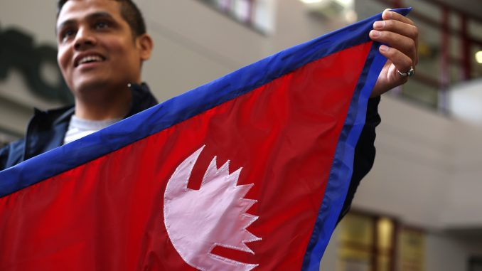 "Buddha Khatri, who is pursuing a doctorate in chemistry, holds a Nepal flag at the Student Center on Friday. Geometric instructions on reproducing a Nepali flag are part of the country's constitution, making it ""the most mathematical flag,"" he said. 