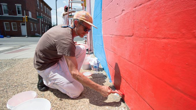 Mural artist MOMO paints for Open Source, a projected created by Mural Arts in Philadelphia. | COURTESY Mural Arts Program