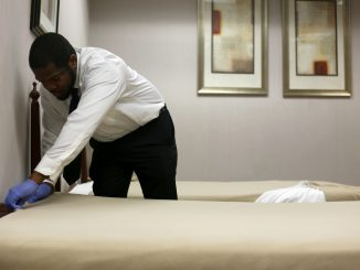 Solomon Jones, a student of the hospitality program at Opportunities Industiralization Center, makes a bed in a mock hotel room as part of the non profit's hands-on training program. | Jenny Kerrigan TTN
