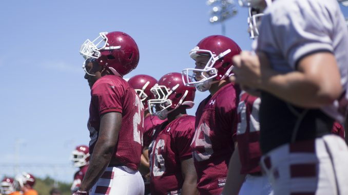The football team stands on the sideline during a practice at Chodoff Field. | Margo Reed TTN