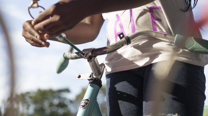 Dashetta Davenport, of Norris Street, fixes her bike at a bike repair station near Paley Library on Aug. 18. | Margo Reed TTN
