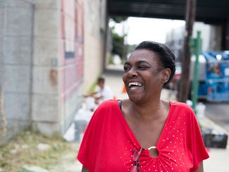 Cinovia Williams, a tenant at the Norris Homes, enjoys the mural which will represent the Norris Homes from 1953 to 2017. | Margo Reed TTN
