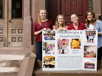 Rachel Makar (left), Mackenzie Blue, Lauren Ravitch and Tori Cuccurullo display a poster detailing Phi Sigma Sigma's philanthropy events for Oct. 5-8. | Joshua Dicker TTN