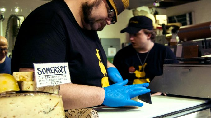 Meltkraft employee, James Lessman (top), slices one of Meltkraft's most popular cheeses, Crema De Blue, for customers to inspect and sample before purchase. All of the cheeses come from the Valley Shepherd Creamery's farm in New Jersey, where over 30 kinds of goat, cow and sheep cheeses are produced. | Brian Tom TTN