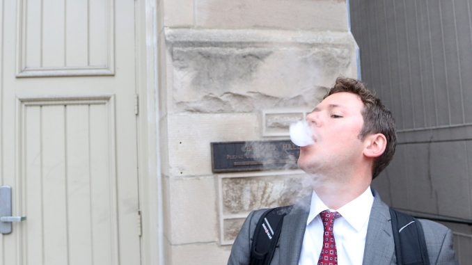 John Basenfelder, a third-year law student, is one of many Temple students who have taken up vaping. Vaping is the common term for using an e-cigarette or vaporizer that heats liquid, which contains nicotine, to produce vapor the user inhales. The practice has been adopted by many former smokers as a healthier alternative to smoking, but some are still skeptical about its benefits. | Evan Easterling TTN
