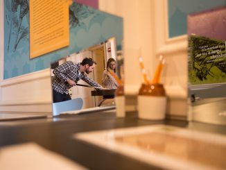 """Jeff Kinslow (left), and Allison Cahill play a game of circular billiards at the """"Alice in Wonderland"""" 150th anniversary exhibit at the Rosenbach Museum. 