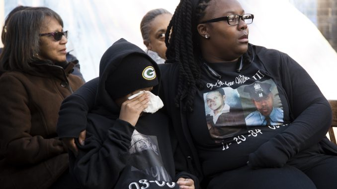 Deja Wolf (right), and her son Quahmier Wolf-Wilson listen to family members speak at Sgt. Robert Wilson III's vigil on March 5. | Brian Tom TTN